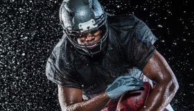 Water splashing on black football player