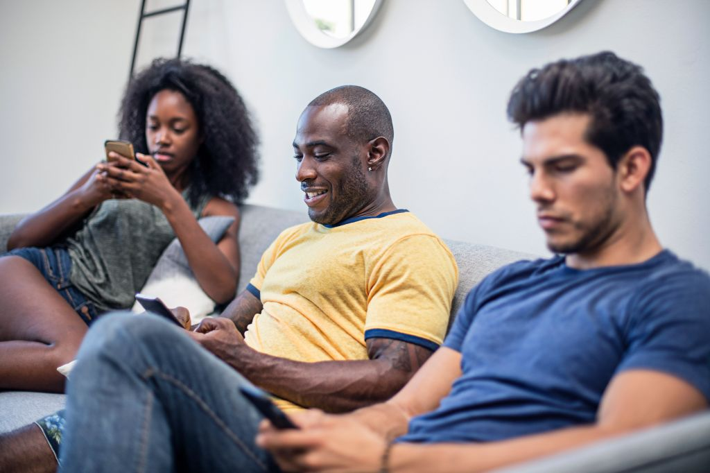 Young friends using smart phones at home