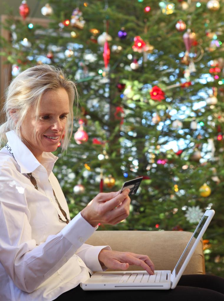 Online Christmas shopping: woman besides xmas tree
