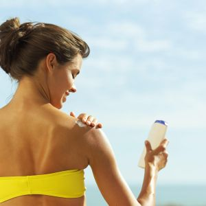 young woman applying sunscreen lotion on her shoulders